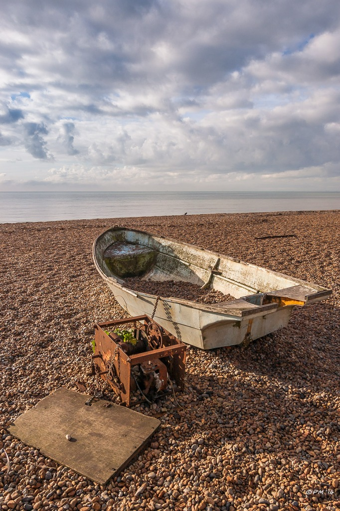 Old rowing boat chained to rusty winch and plywood board sitting on Brighton Beach, UK 2014 P.Maton eyeteeth.net