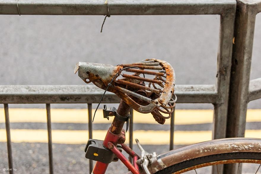 Old Rusty Bicycle saddle railings roadside closeup