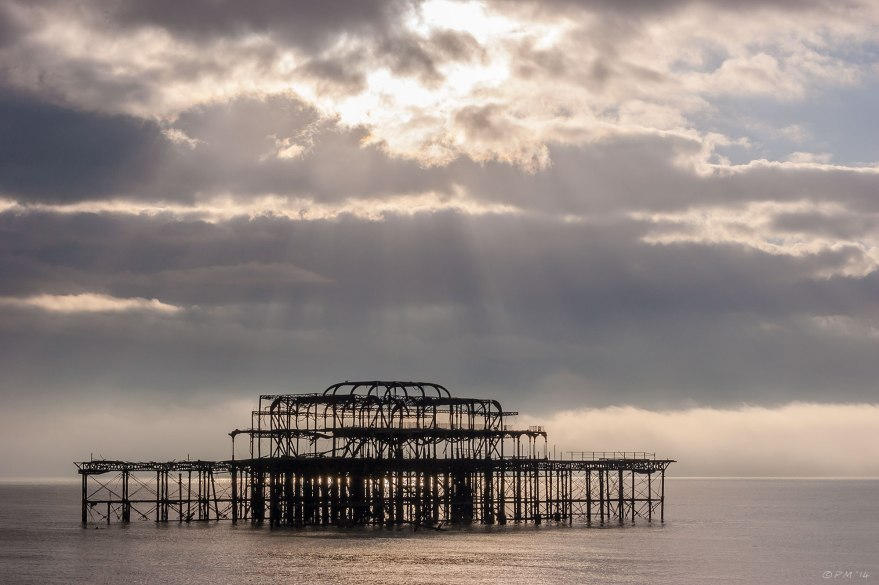 Ruins of West Pier Brighton, silhouette, clouds with sun rays onto sea. 2014 eyeteeth.net