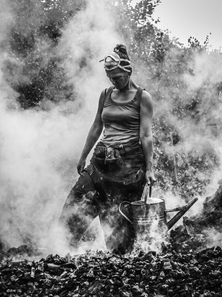 Woman dousing embers in charcoal heap with watering can. Coppice Week, Wildwood, Ashdown Forest, Charcoal Burning, monochrome.