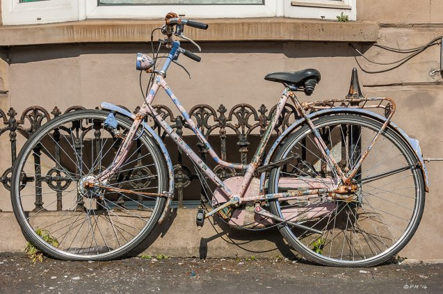 Old rusty bicycle with peeling pink and blue paint  and flat tyres leans against railings in front of house Brighton UK  29-4-2014 eyeteeth.net