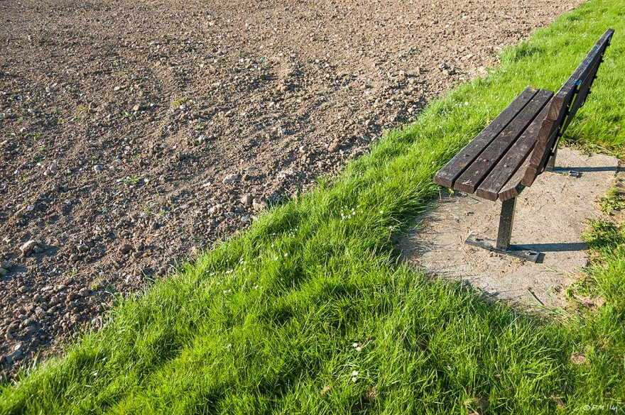 Bench on green grass facing ploughed bowling green Preston Park Brighton, colour, abstract, 2014 eyeteeth.net