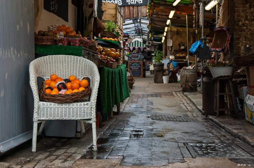 Diplock's Yard, Brighton Farm Market, wicker chair with basket of oranges on wet flagstones with market in background North Laine Brighton street photography 2014 eyeteeth.net