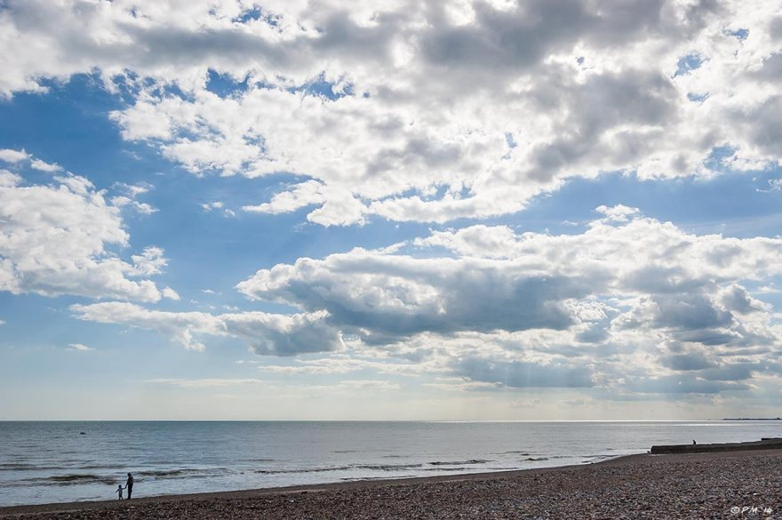 Mother and child holding hands silhouette at waters edge on shingle beach with large expanse of blue shy with scattered cloud and rays of sun, Hove seafront UK 2014 eyeteeth.net