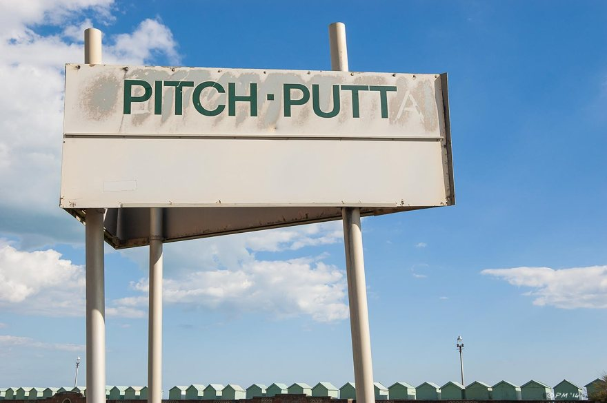 Pitch-Putt sign with blue sky clouds and row of beach huts in background Hove Lagoon Sussex 2014 eyeteeth.net