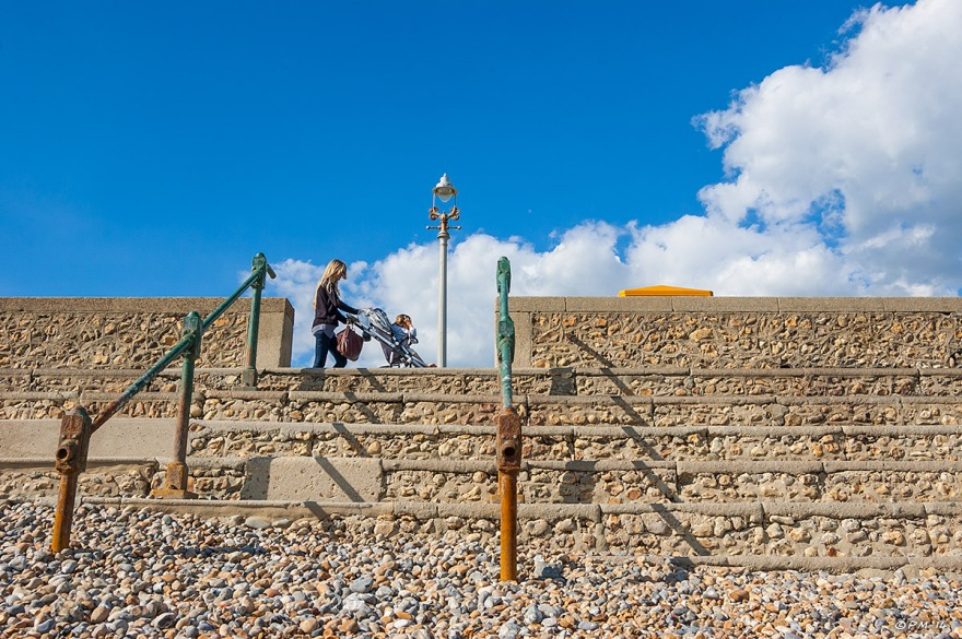 Mother pushing child in pram side profile against blue sky with cloud on Hove seafront promenade sussex, victorian steps lamp and  rails. 2014 eyeteeth.net
