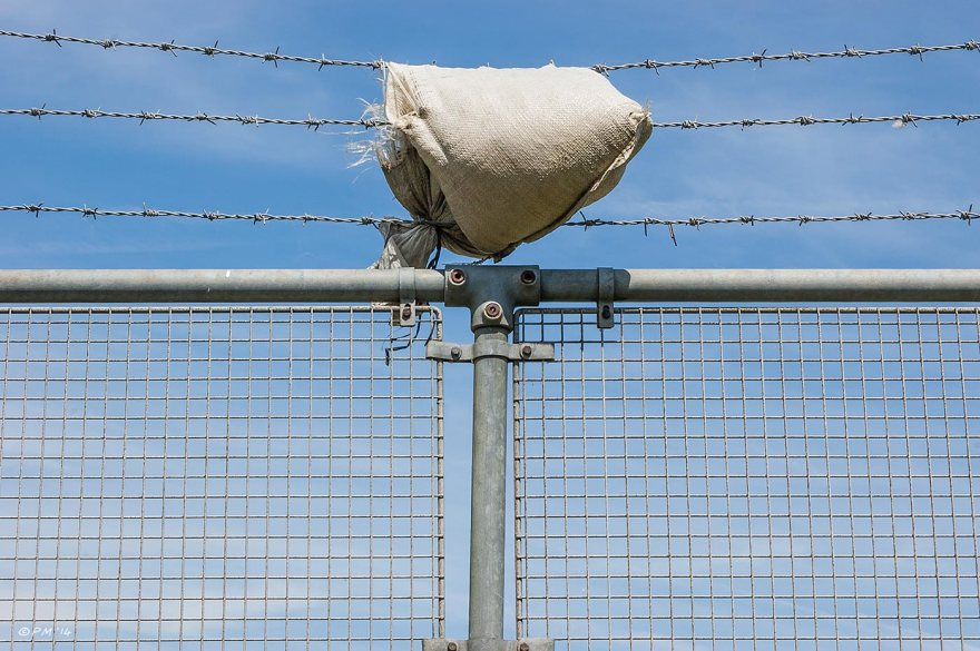 Sand bag draped over barbed wire on top of wire mesh fence against blue sky & light cloud, abstract urban, Brighton 2014 eyeteeth.net