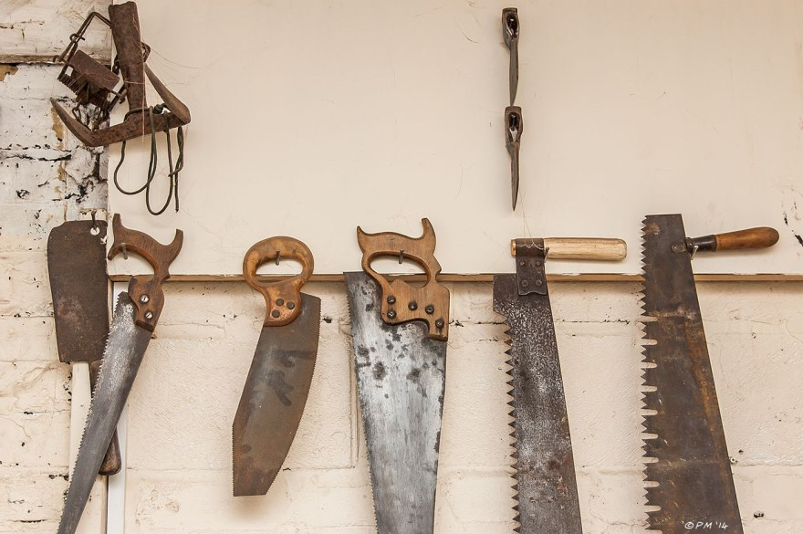 Old Saws hanging on workshop wall with Gin Trap Meat Cleaver and axe heads on cream background Coachwerks Brighton UK 2014 eyeteeth.net
