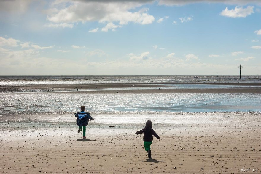 Two children running away down beach towards sea in silhouette sunshine blue sky and birds, Littlehampto West Sussex UK 2014 eyeteeth.net