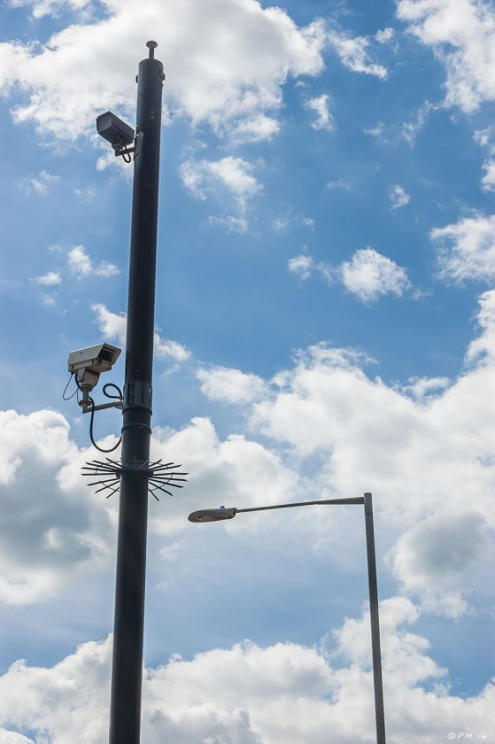 CCTV Surveillance Cameras on pole next to street lamp against blue sky with broken cloud colour silhouette street security Hove UK 2014 eyeteeth.net