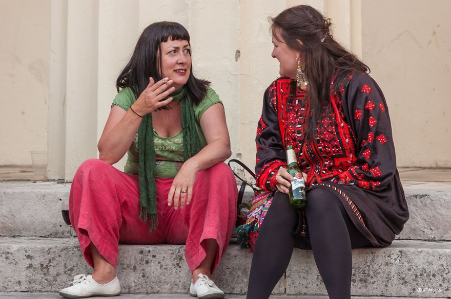 Two female 'gypsy' performers in bright costumes sit on steps drinking and smoking Brighton Street Photography 2014 eyeteeth.net