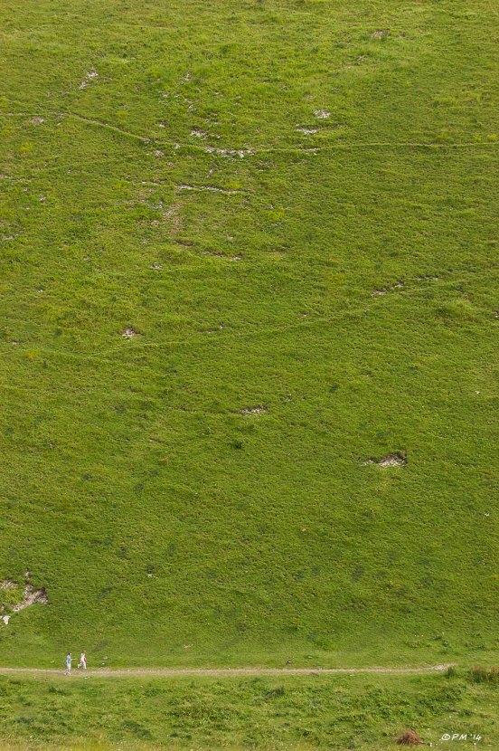 two people walking along trail  in bottom of Devils Dyke, dwarfed by grassy hillside, abstract. East Sussex, Britain. P.Maton 2014 eyeteeth.net