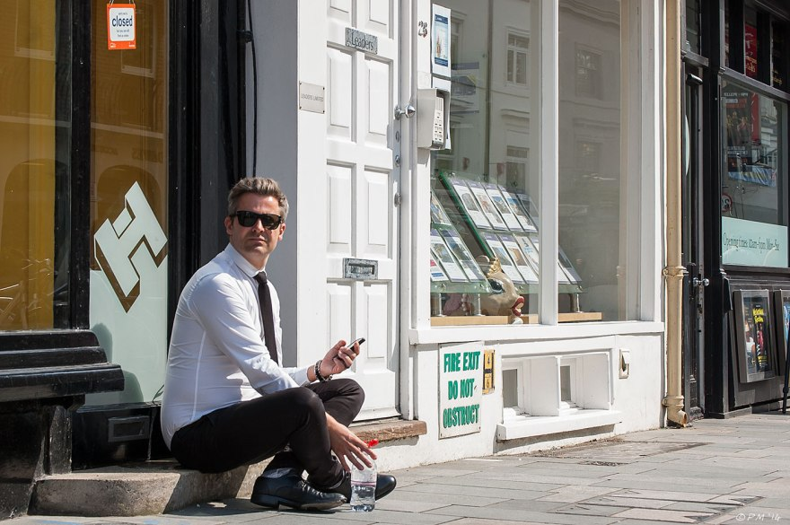 An estate agent sits in sun looking at camera with phone and bottle of water in hand on step outside business shop front brighton street photography UK 2014 eyeteeth.net