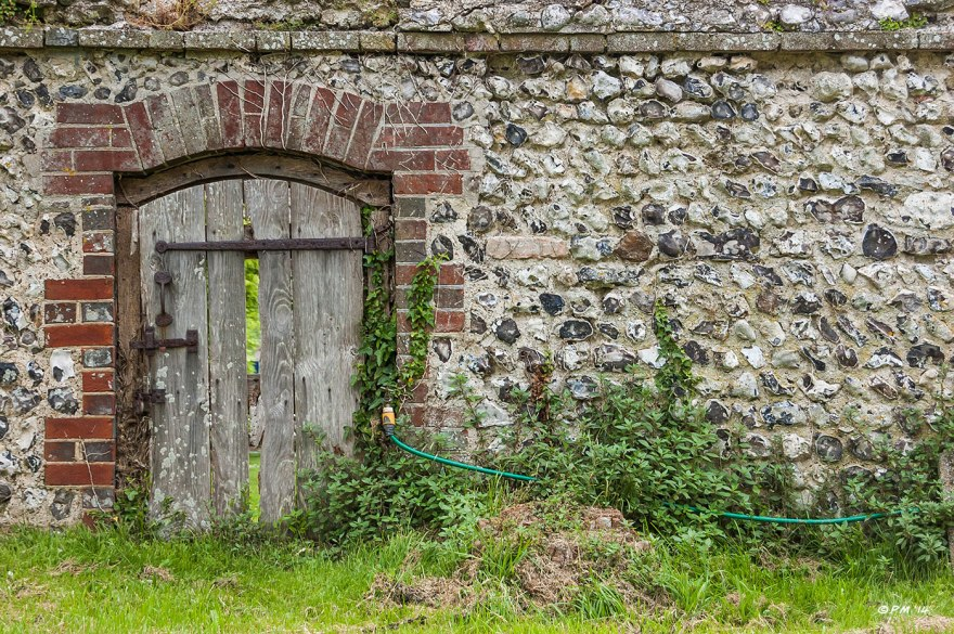 Knapped Flint Wall and small old wooded door leading to Glynde Place from St Mary's Church yard, water tap & hosepipe. Glynde Place East Sussex 2014 eyeteeth.net