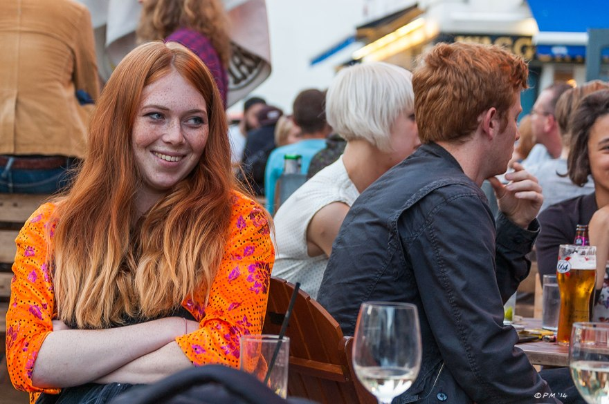Red haired young woman in orange blouse smiling at friends outside Miss Fitzherberts Pub, Brighton, UK 2014 eyeteeth.net
