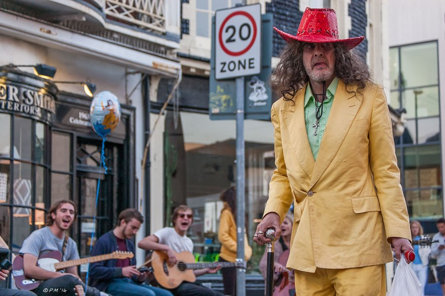 Man in red sequin stetson and yellow suit with cane and shopping bag buskers playing in background New Road Brighton UK 2014 eyeteeth.net