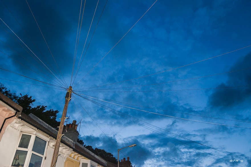 Telegraph wires radiating from pole against dark blue cloudy sky at dusk with illuminated houses  abstract Brighto Argyle Road 2014 eyeteeth.net