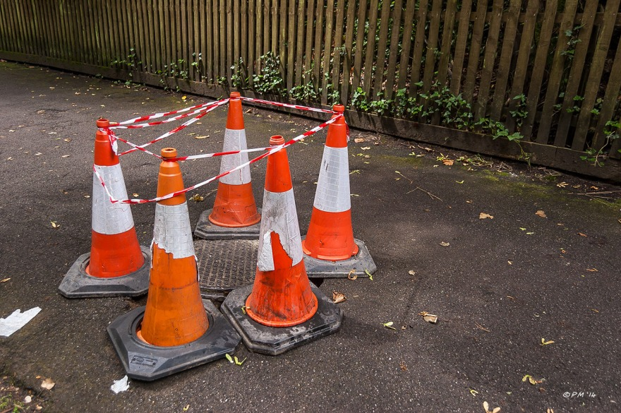 Traffic cones and tape around man hole cover in path Alum Chine Westbourne, Bournemouth P. Maton 2014 eyeteeth.net