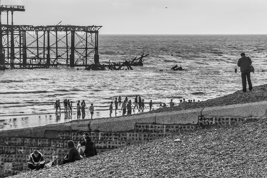Monochrome People on Brighton Beach with West Pier in background  Sussex UK P.Maton 2014 eyeteeth.net