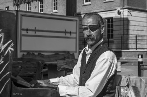Man in shirt and waistcoat with eye patch and moustache playing piano in Trafalger Street Brighton UK monochrome busker P. Maton street photography 2014 eyeteeth.net