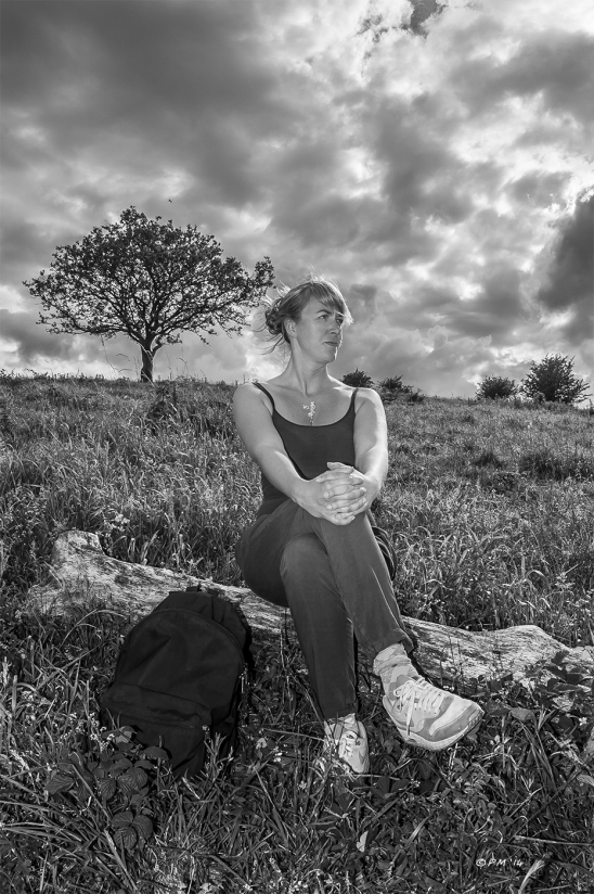 Woman sits on sun bleached tree trunk on Devils Dyke under dramatic cloudy sky Monochrome Sussex UK 2014 P.Maton eyeteeth.net