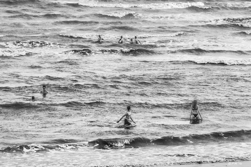 Monochrome swimmers walking in the surf on Brighton Beach, East Sussex. UK P.Maton 2014 eyeteeth.net