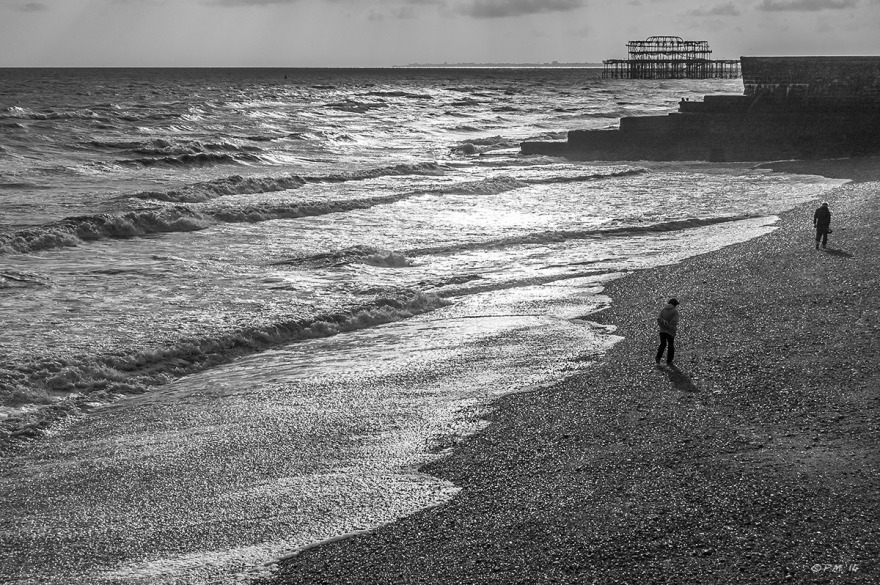 Two figures walking on Brighton Beach with Groyne and West Pier ruin in background Monochrome landscape P.Maton 2014 eyeteeth.net