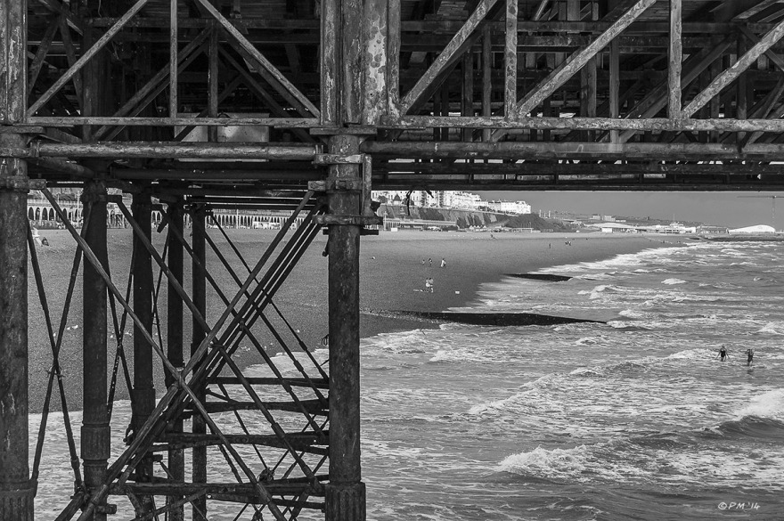 View under Brighton Palace Pier East along seafront towards Brighton Marina Village with rusty metal structure in foreground, Monochrome landscape abstract Brighton East Sussex UK P.Maton  2014 eyeteeth.net
