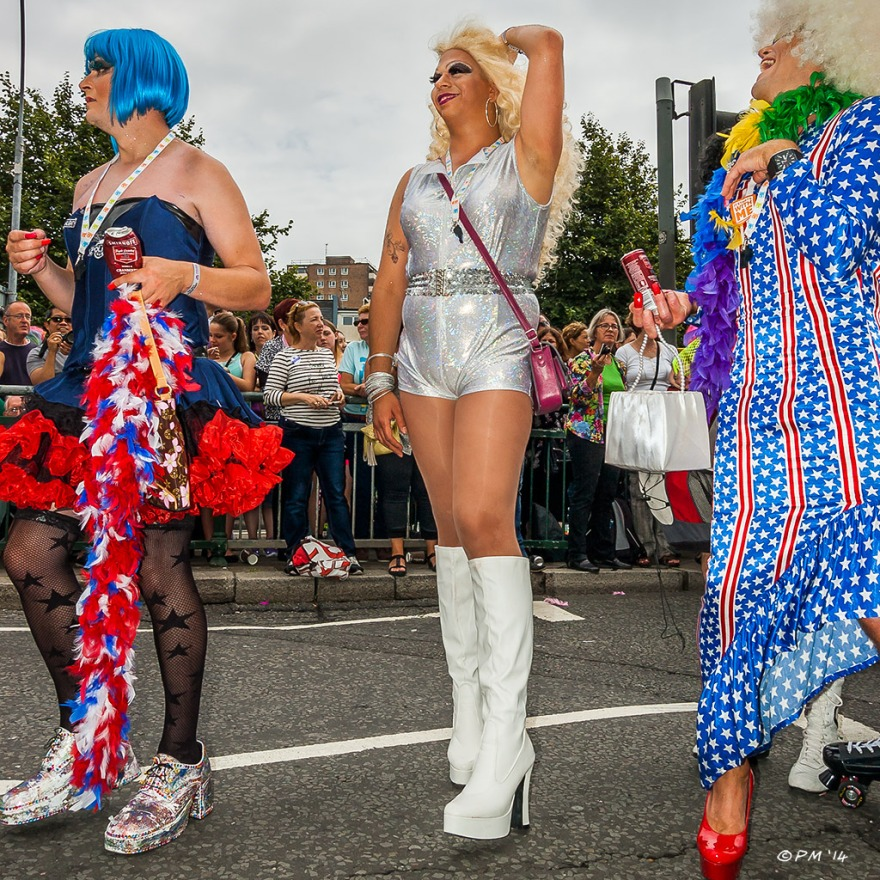 Three drag queens in parade at Gay Pride Brighton UK with onlookers in background P. Maton 2014