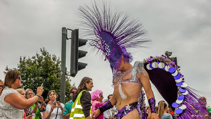 Man with purple head dress in parade at Gay Pride Brighton UK with onlookers in background P. Maton 2014