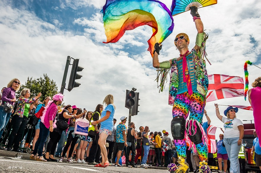 Man in rainbow costume on rollers kates waving rainbow fan in parade at Gay Pride Brighton UK P. Maton 2014