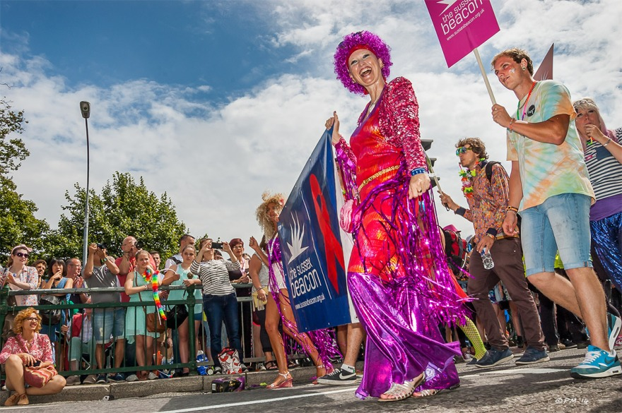 Lady with sequin dress and purple hair, Sussex Beacon in parade at Gay Pride Brighton UK with onlookers in background P. Maton 2014 eyeteeth.net