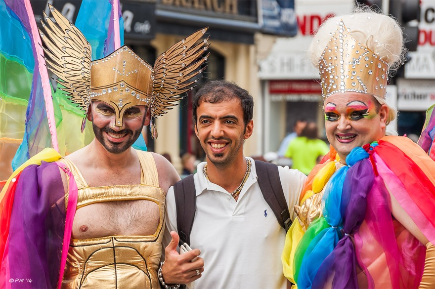 Man posing for photograph with two flamboyantly dressed members of the parade at Gay Pride Brighton UK P. Maton 2014