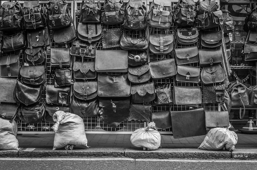 Wall of leather handbags and backpacks hanging on display outside a shop on Sydney Street, Brighton, UK. Monochrome. P.Maton 2014 eyeteeth.net