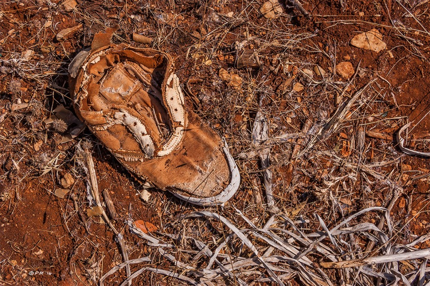 Abandoned old boot in red soil with dead grasses, colour. Patara Gelemis Turkey. P.Maton 2014 eyeteeth.net