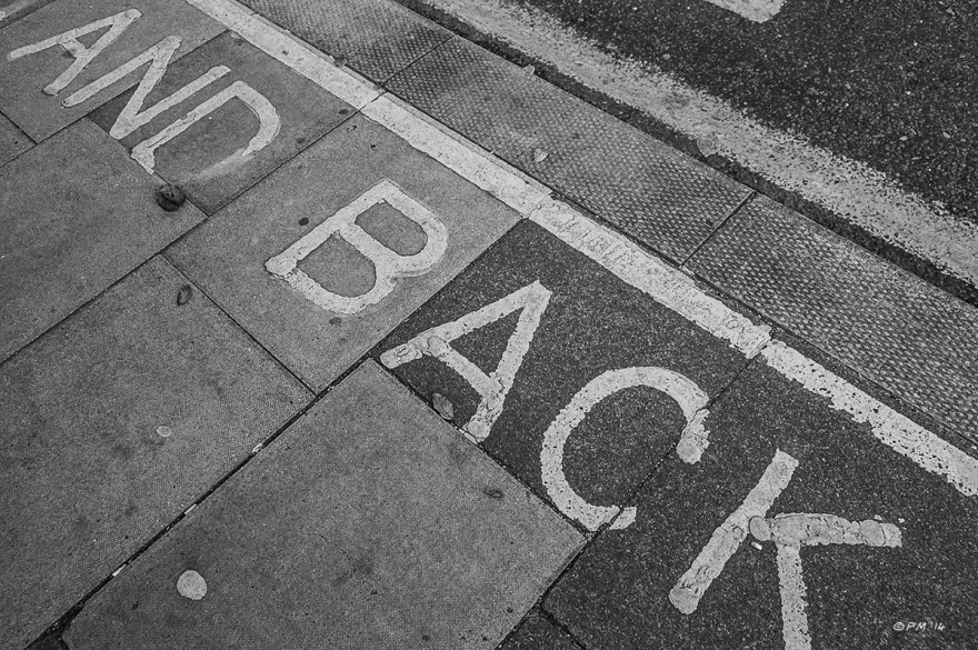 Writing on pavement (sidewalk) at bus stop '...AND BACK' Monochrome abstract landscape. © P.Maton 2014 eyeteeth.net