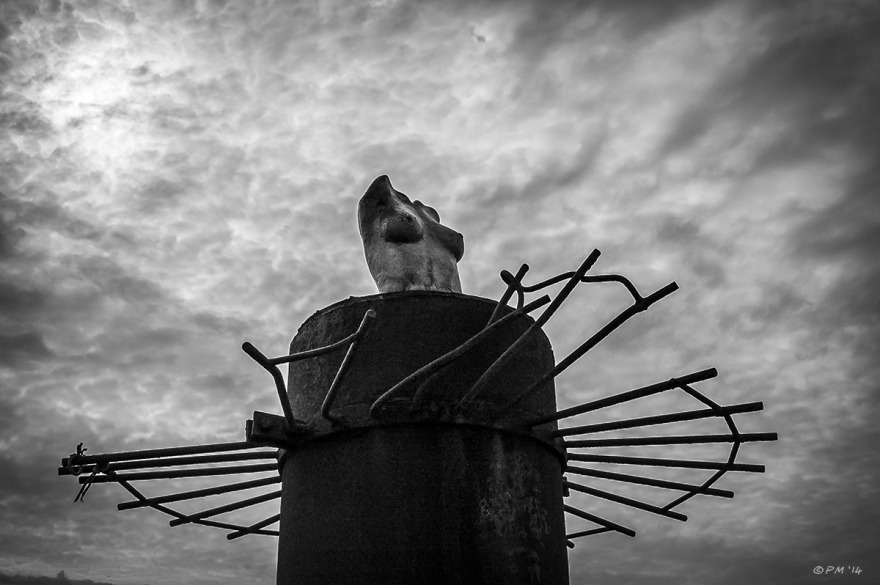 Female bust sculpture on top of West Pier foundation post against cloudy sky with sun in background, Brighton Beach. Monochrome landscape abstract. Brighton UK. P.Maton 2014 eyeteeth.net