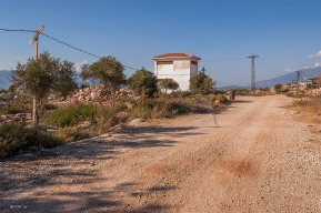 Overhead cables leading to solitary building by dirt road. Patara Turkey. Landscape Colour. P.Maton 2014 eyeteeth.net