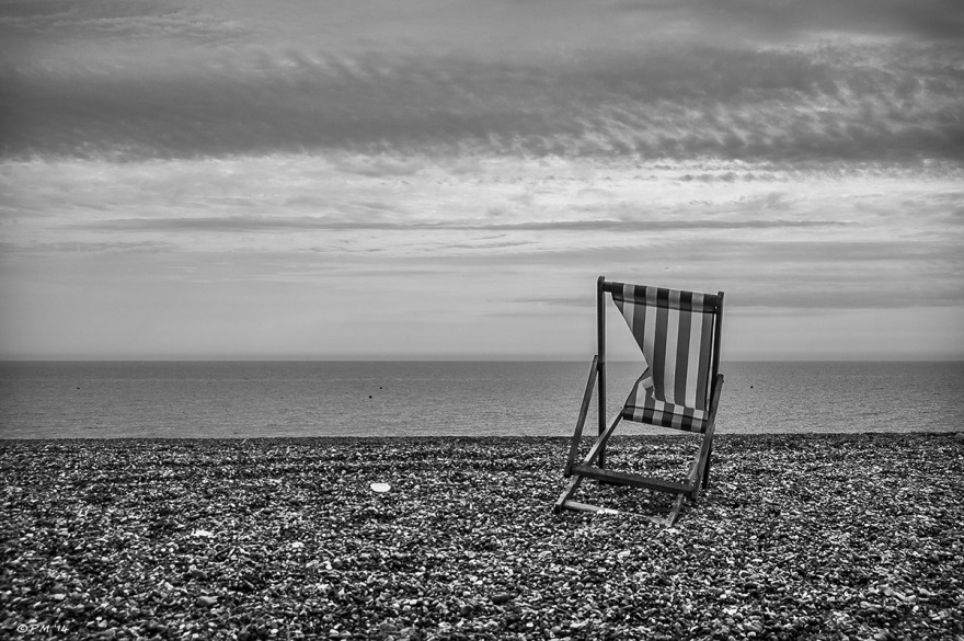 Buckled deck chair with stripes on shingle on Brighton Beach. Monochrome landscape. P.Maton 2014 eyeteeth.net