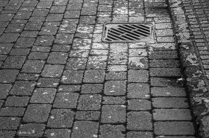 Wet drain on stone path lit by morning sun. Monochrome abstract. Brighton East Sussex UK. P.Maton 2014 eyeteeth.net