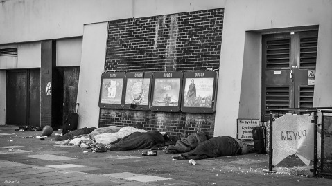 Homless people asleep in sleeping bags below film advertising in front of Odeon cinema. Monochrome landscape. Brighton East Sussex UK. P.Maton 2014 eyeteeth.net