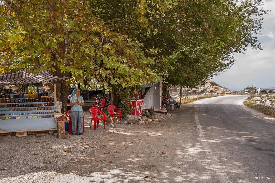 Lady Selling Honey on roadside under tree. Tlos, Turkey. Colour Landscape. P.Maton 2014 eyeteeth.net