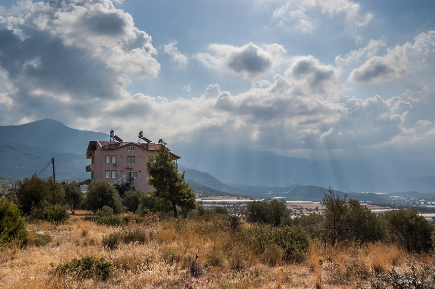 House with solar panels on hill overlooking Xanthos Valley with mountains in background and sun rays through clouds. Turkey. Colour Landscape. P.Maton 2014 eyeteeth.net