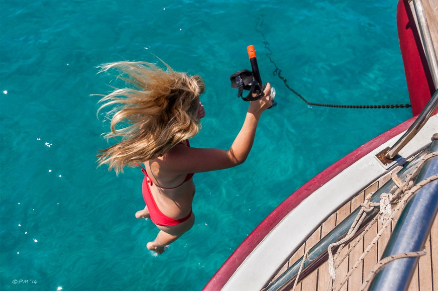 Woman jumps from boat into sea holding mask and snorkel. Kalkan, Turkey. Colour. P.Maton 2014 eyeteeth.net