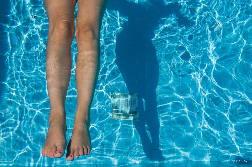 Womans legs in swimming pool with shadow cast on pool floor. Colour abstract. P.Maton 2014 eyeteeth.net