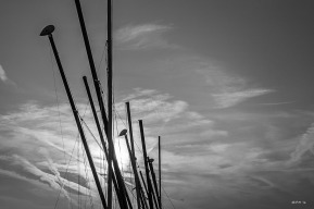 Sailing boat masts with rising sun and cloud with con-trails. Monochrome abstract. Brighton East Sussex UK. P.Maton 2014 eyeteeth.net