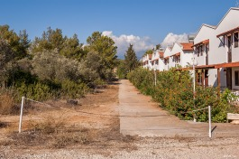 Empty new build housing block bordering olive trees and scrub. Patara Turkey. Landscape Colour. P.Maton 2014 eyeteeth.net