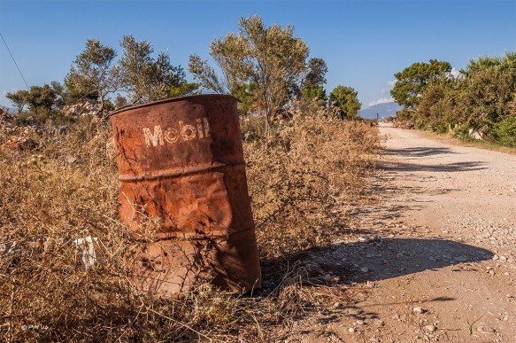 Rusty Mobil oil drum in brush beside dirt road. Patara Turkey. Landscape Colour. P.Maton 2014 eyeteeth.net
