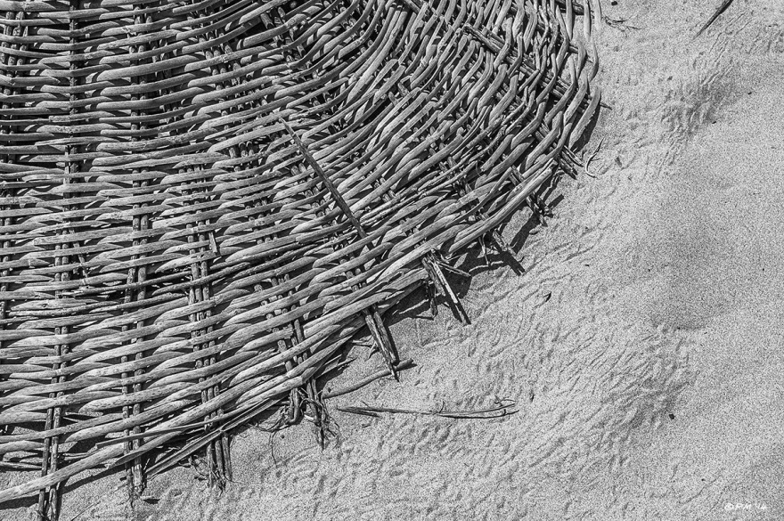 Woven Parasol sun shade lying on sand with crap tracks, Gelemis, Patara, Turkey. Abstract closeup monochrome. P.Maton 2014 eyeteeth.net