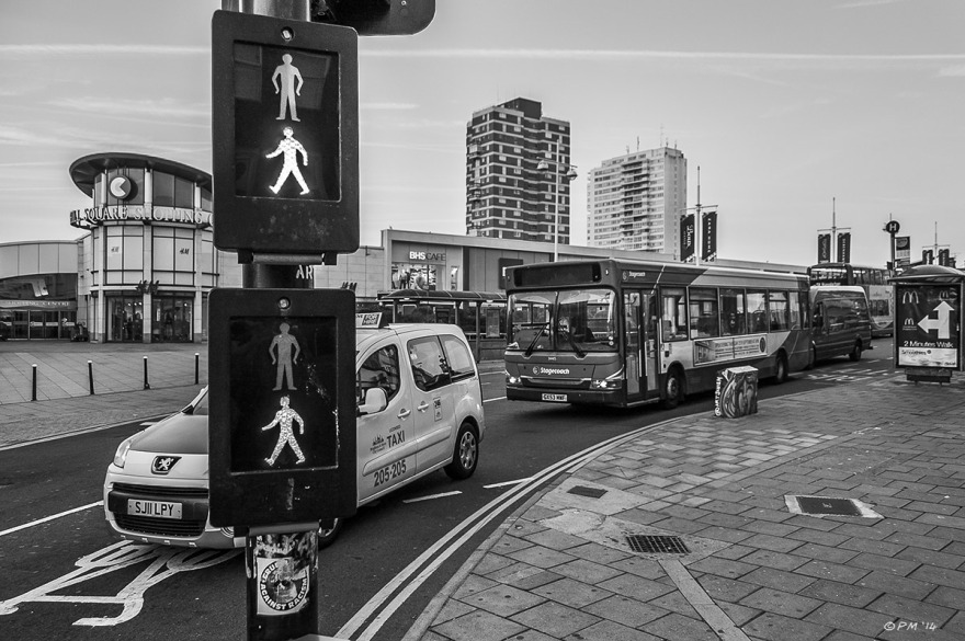 Pedestrian crossing signalling it is safe to cross road, taxi and bus in background with view of Churchill Square shopping centre and high rise apartments. Monochrome Landscape. Brighton UK. P.Maton 2014 eyeteeth.net